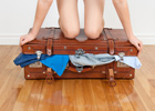 Photo: Girl kneeling on a full suitcase