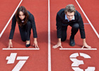 Photo: Business man and woman in starting positions on a racetrack