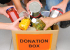 Photo: People putting tins of food into a donation box